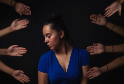 woman surrounded by hands offering help